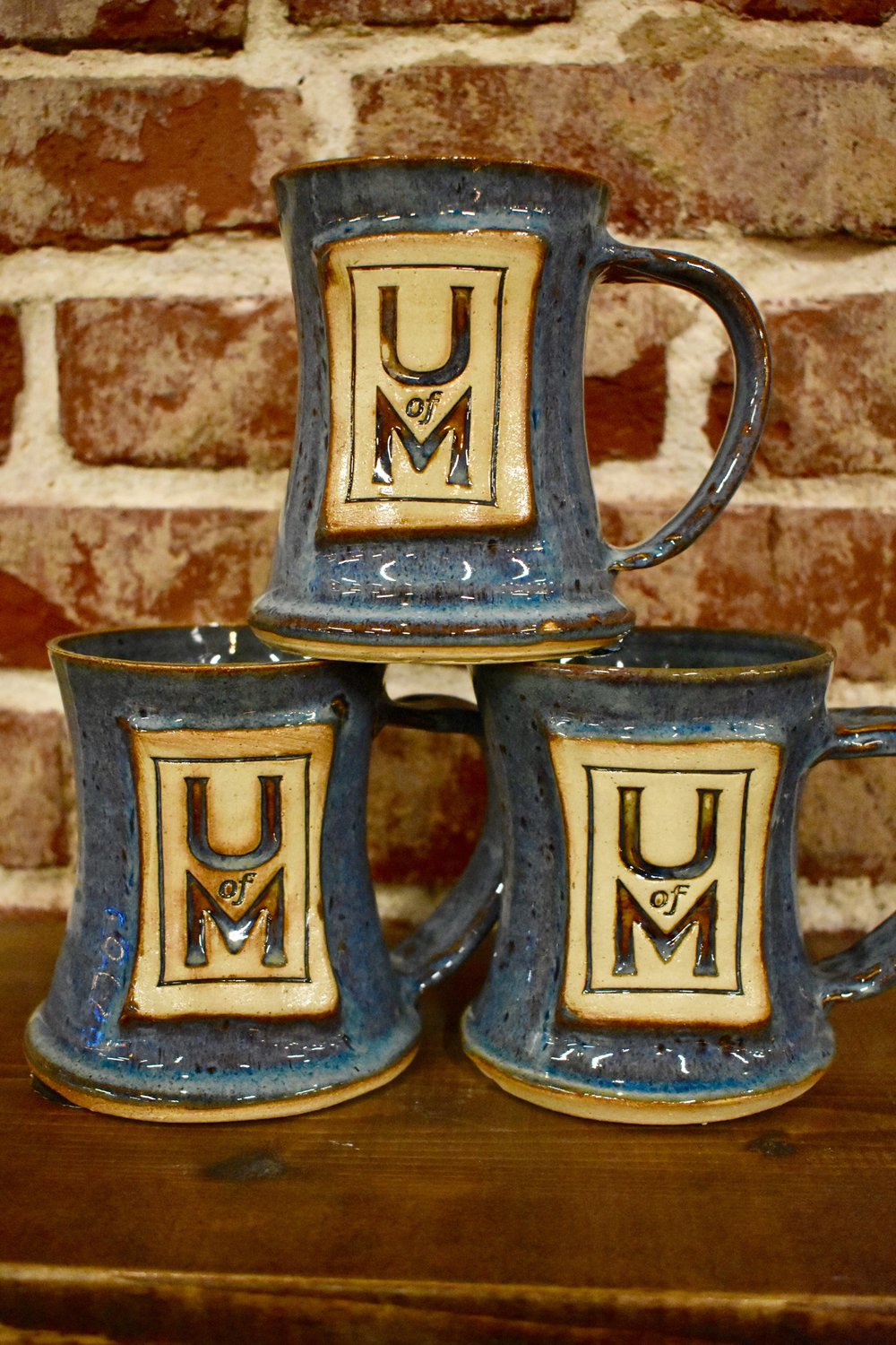 A set of U of M mugs created at The \Belltower Artisans+